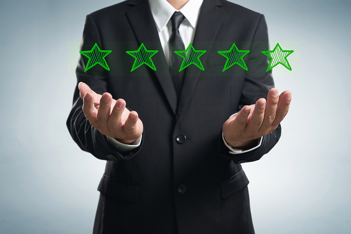 Businessman holding five star rating.